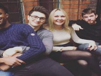 Dalton Harris sitting in the lap of fellow X Factor contestant Brendan Murray