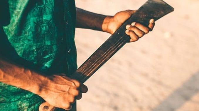 Jamaica man holding machete.